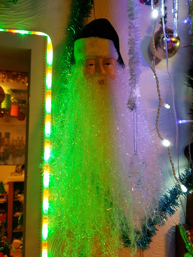 Santa hanging on wall with beard lit by green light