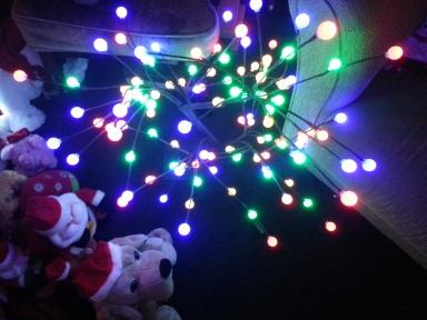 Santa toys look at a tree made up of lights