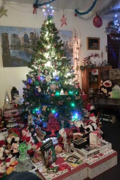 Christmas tree lit up surrounded by presents and toys