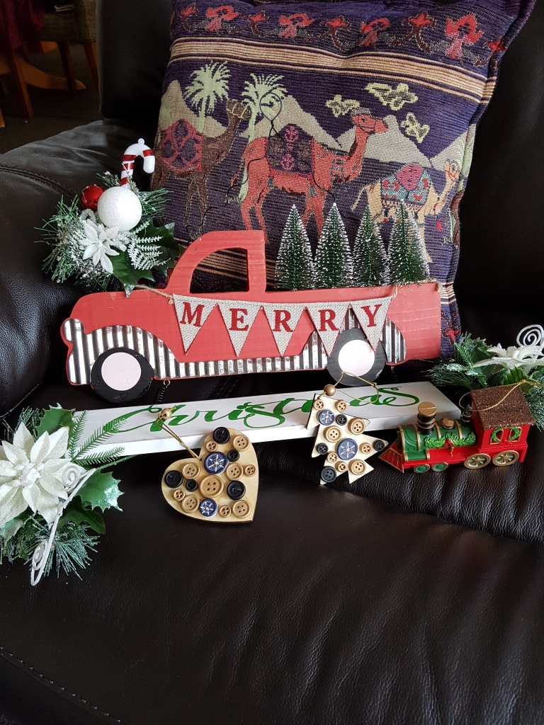 Merry Christmas sign, a wee wooden train and a few other decorations to hang on a tree. Includes a tree and and a heart made of wood and adorned with buttons