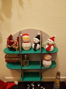 Small shelving unit of ornaments, mostly snowmen