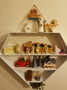 Shelves of small ornaments including nativity scenes and a train of camels (wood)