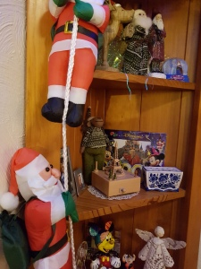 Santas climbing down - or up? - a rope; shelves in background display various Christmas figures