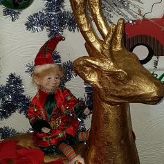 Red and green elf riding a gold reindeer
