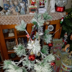 Small snowy pine tree with ornaments and an arrany of ornaments and a china nativity set behind