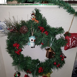 Wreath with ornaments including an owl and a copper kettle