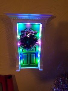 Miniature front door, lit up and decorated with a wreath