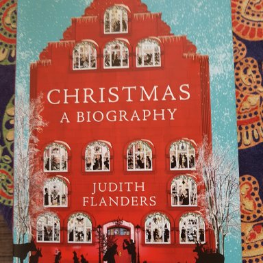 Book cover of a red house in a snowy landscape. 'Christmas: a biography' by Judith Flanders