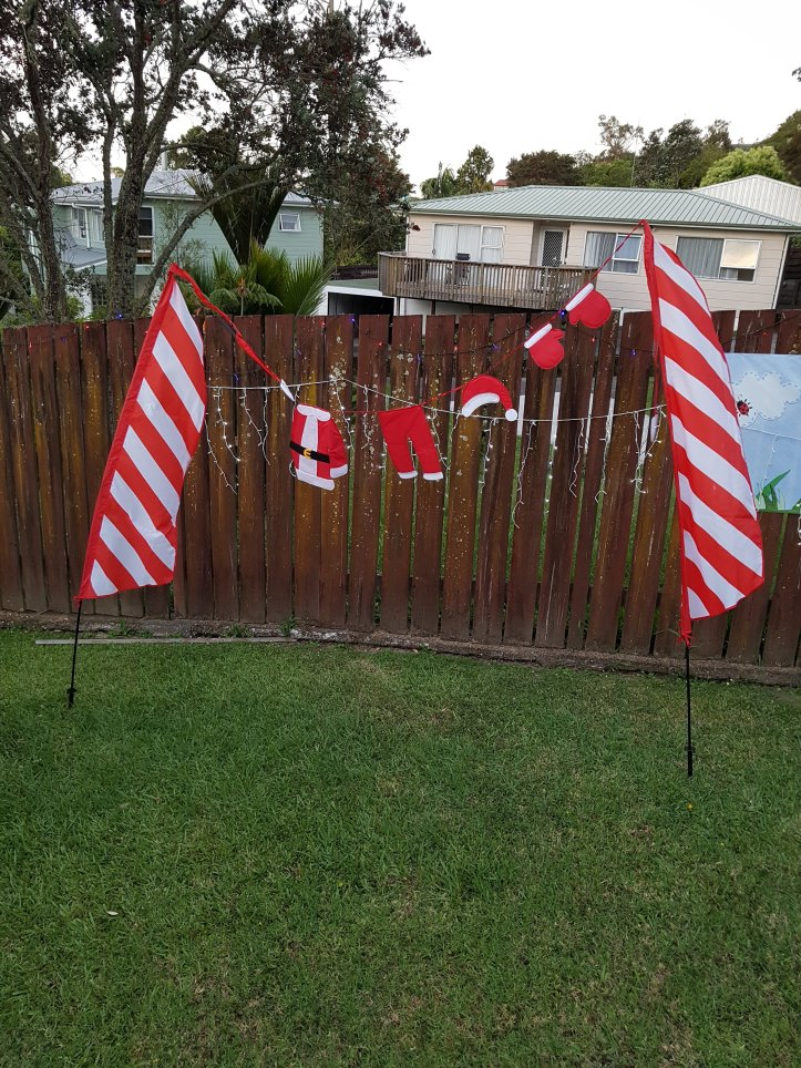 Washing line of Santa outfit between two red and white flags