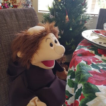 Monk puppet sitting on a dinging room chair; Xmas tablecloth and a tree in the background