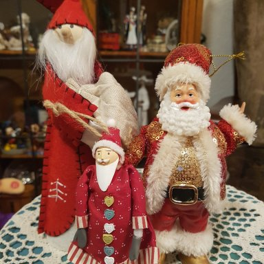 Three red Santas; a standing one in red felt and two sparkly hanging Santas
