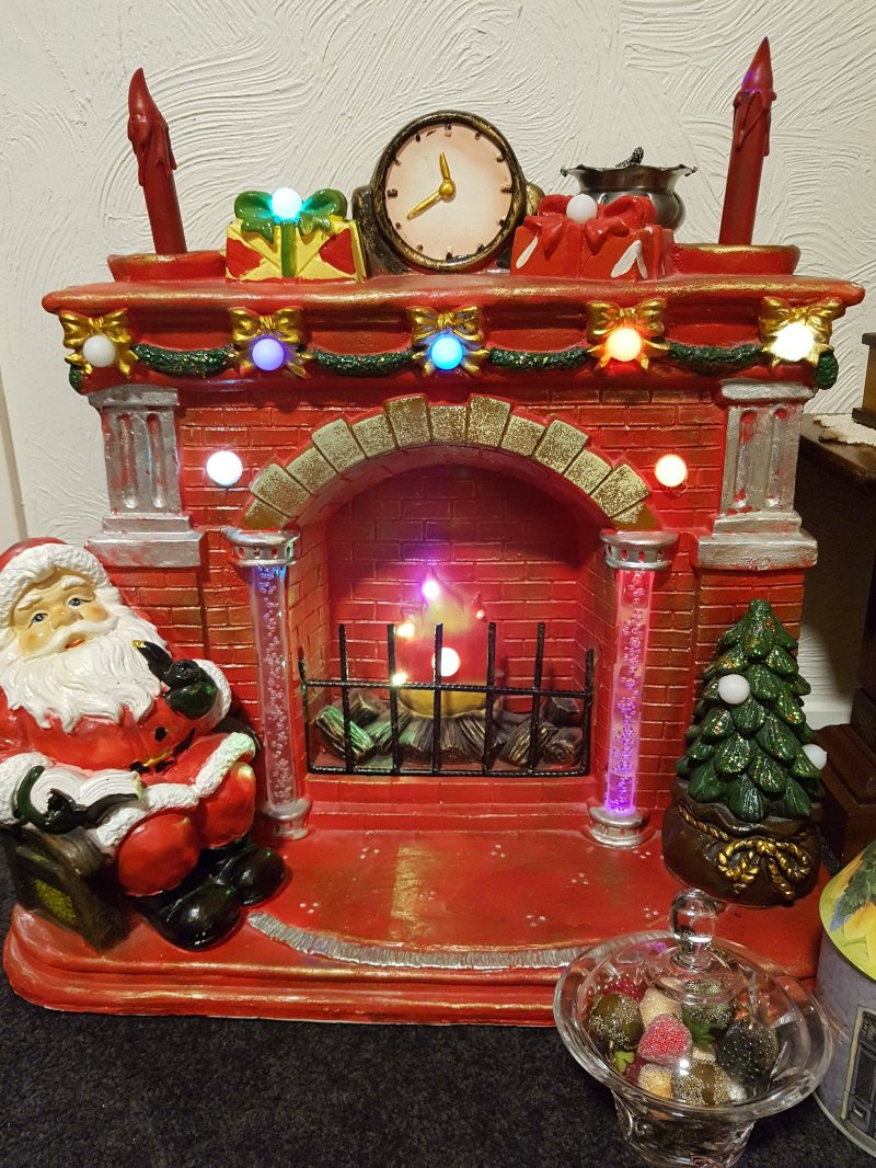 Large light up fireplace with mantel and Santa in a rocking chair