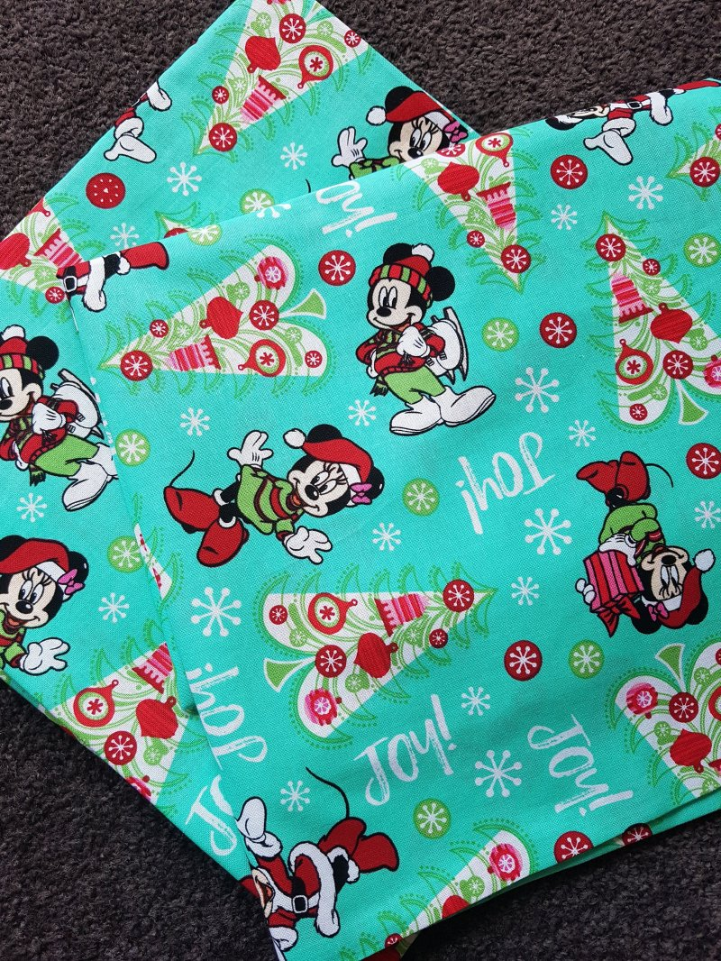 Pillow cases featuring the word Joy! and Christmas trees and Mickey and Minnie Mouse