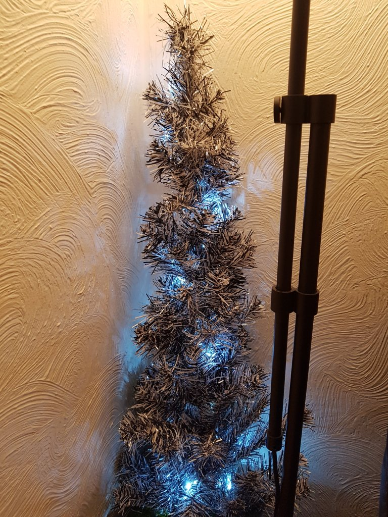 Silver and black Xmas tree, lit; beside a lamp stand