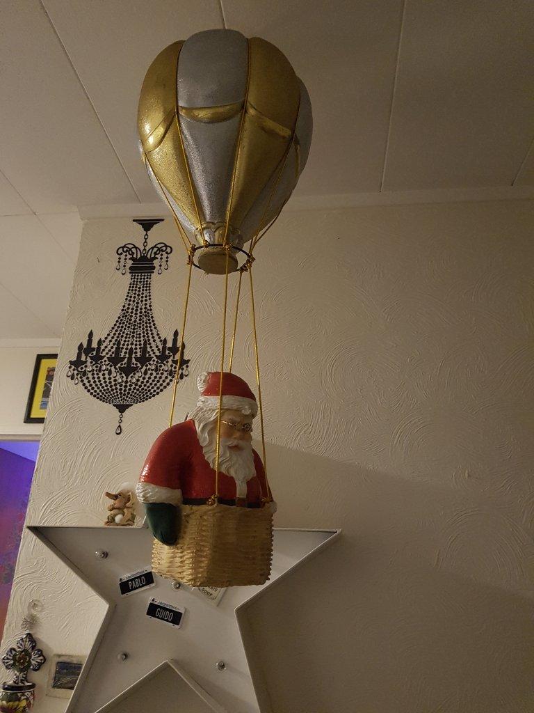 Santa in the basket of a hot air ballon, looking downwards