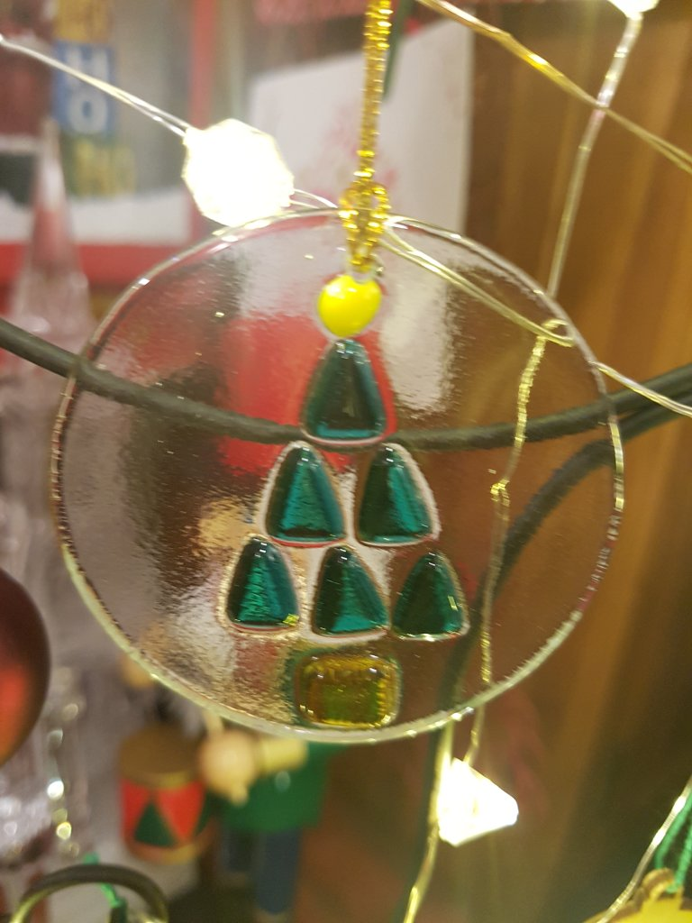 Glass hanging ornament featuring a green tree