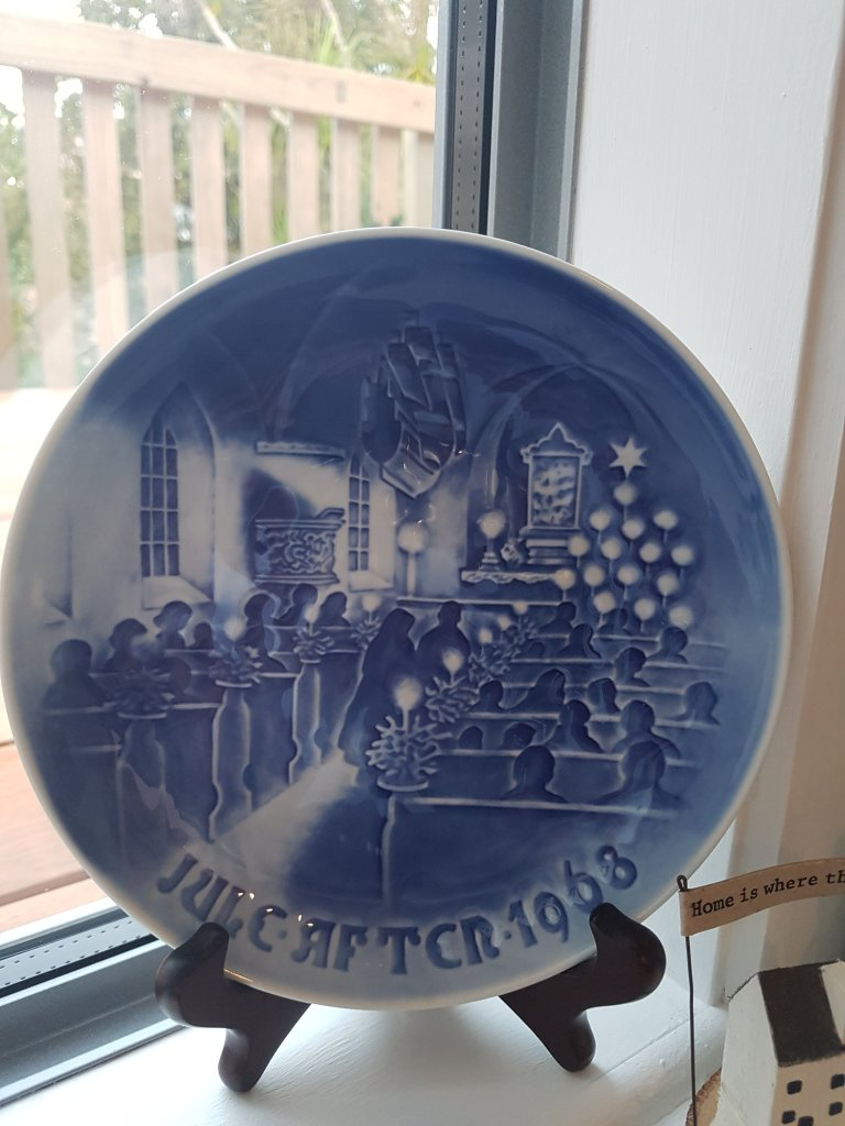 Blue plate featuring the interior of a church and worshippers at Christmas