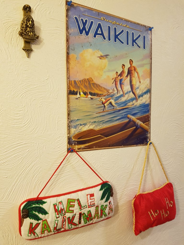 Fabric sign saying Merry Christmas (Hawai'i style) under a sign of the surf beach at Waikiki