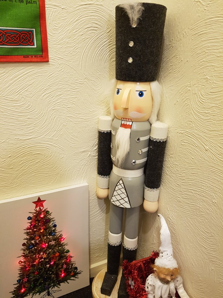 Large wooden nutcracker, elf and lit up picture of a Christmas tree