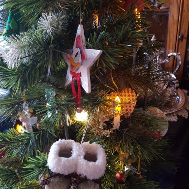 Christmas tree with Donald Duck ornament and little fur-topped boots; lit up candles