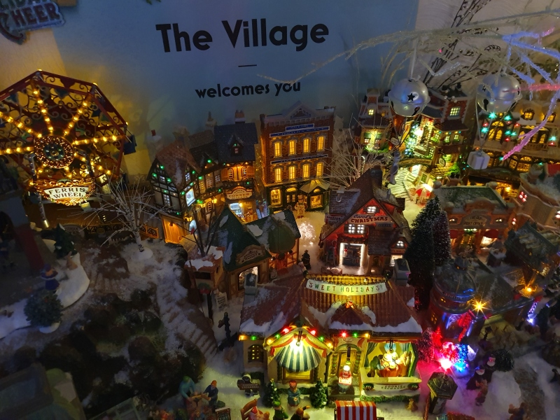 Village view (including ferris wheel) and a sign above: 'The Village welcomes you'