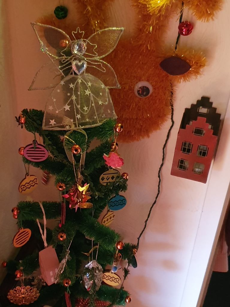 Small decorated green tree and silver angel; weird reindeer face on the wall behind