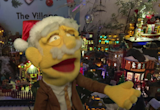 Professor Hans Von Puppet in a santa hat, standing in front of the lit up Village