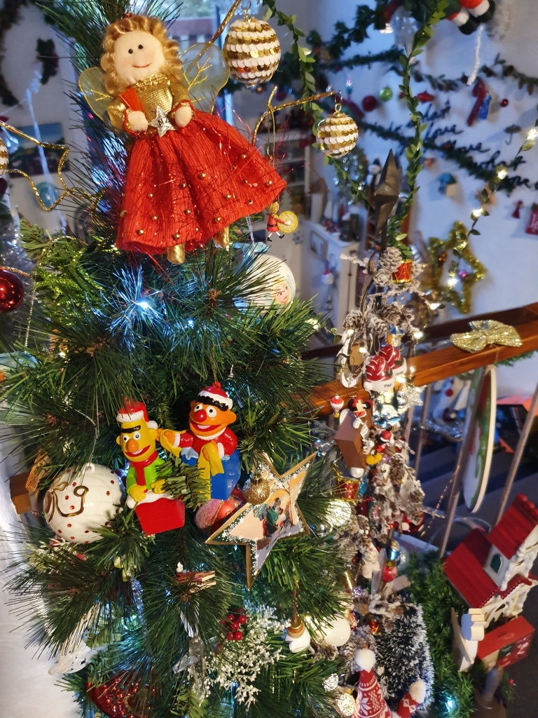 Medium size green tree; red dress angel on top; Bert and Ernie hanging together