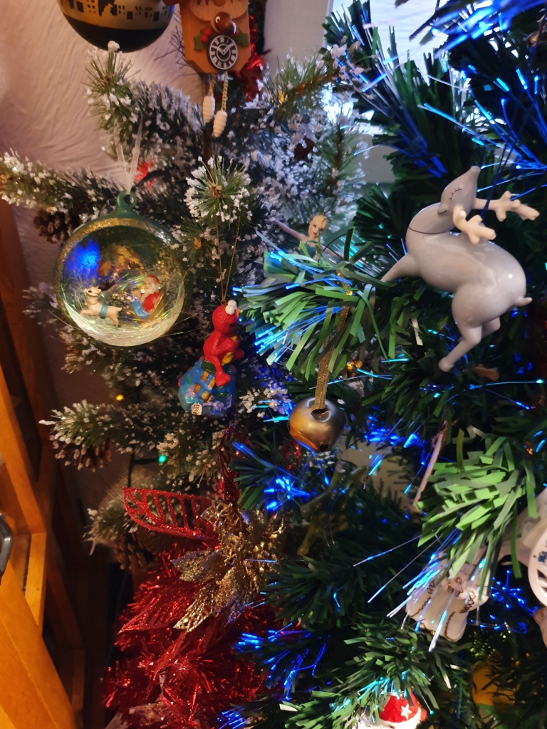 Two decorated trees; Christmas reindeer ornament, nativity scene and an Elmo ornament are prominent