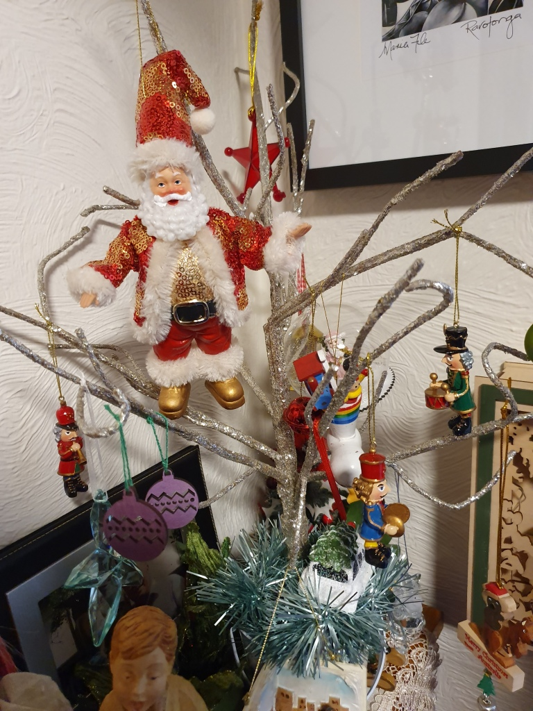 Small tree of glittery branches; ornaments including a fairly big Santa