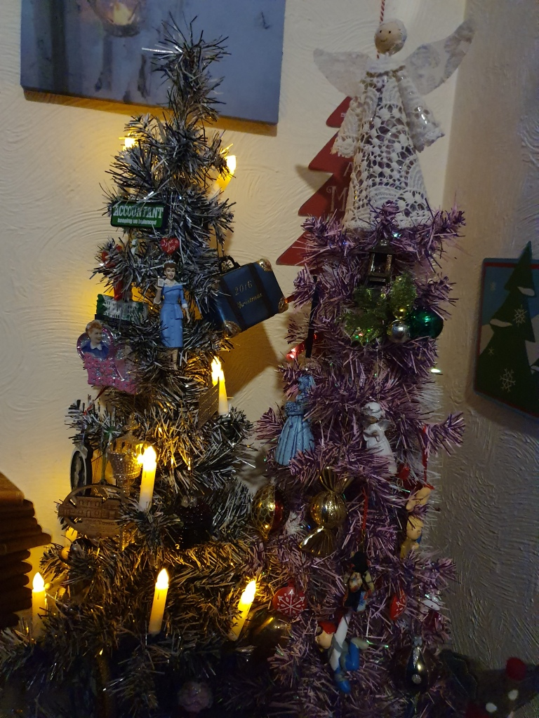 Two medium size trees, one lit with candles