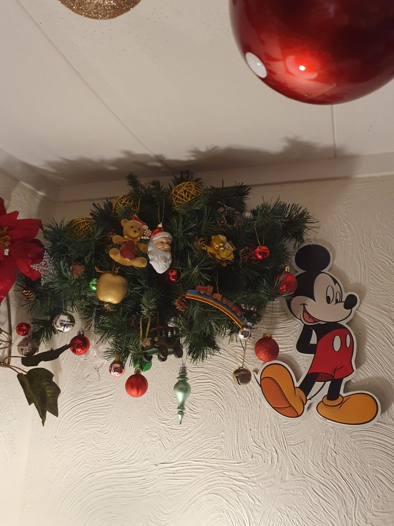 Tree ornaments on tree boughs at the top of a wall, near the ceiling; a metal Mickey Mouse smiles at us