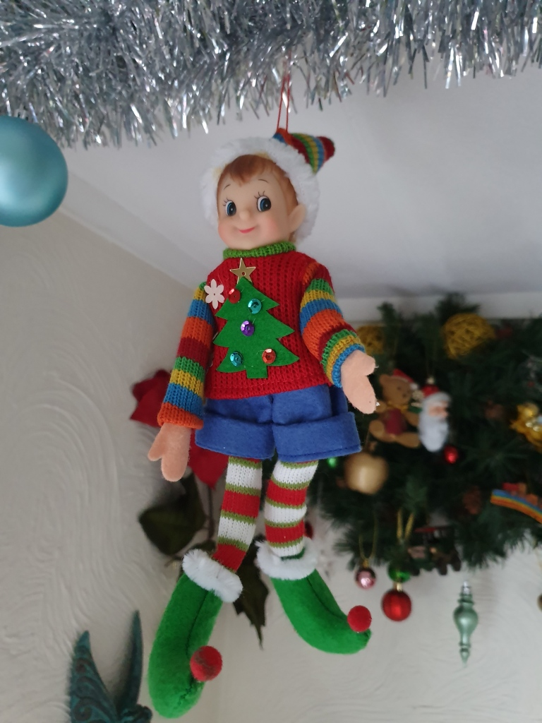 Young elf in bright jumper, shorts, coloured stockings and red shoes