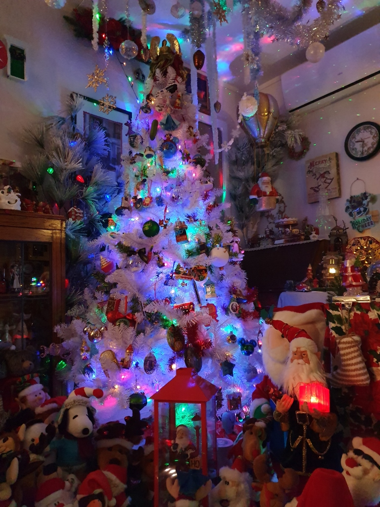 Tall white tree, lit; Santas and toys, including a Santa in a hot air balloon