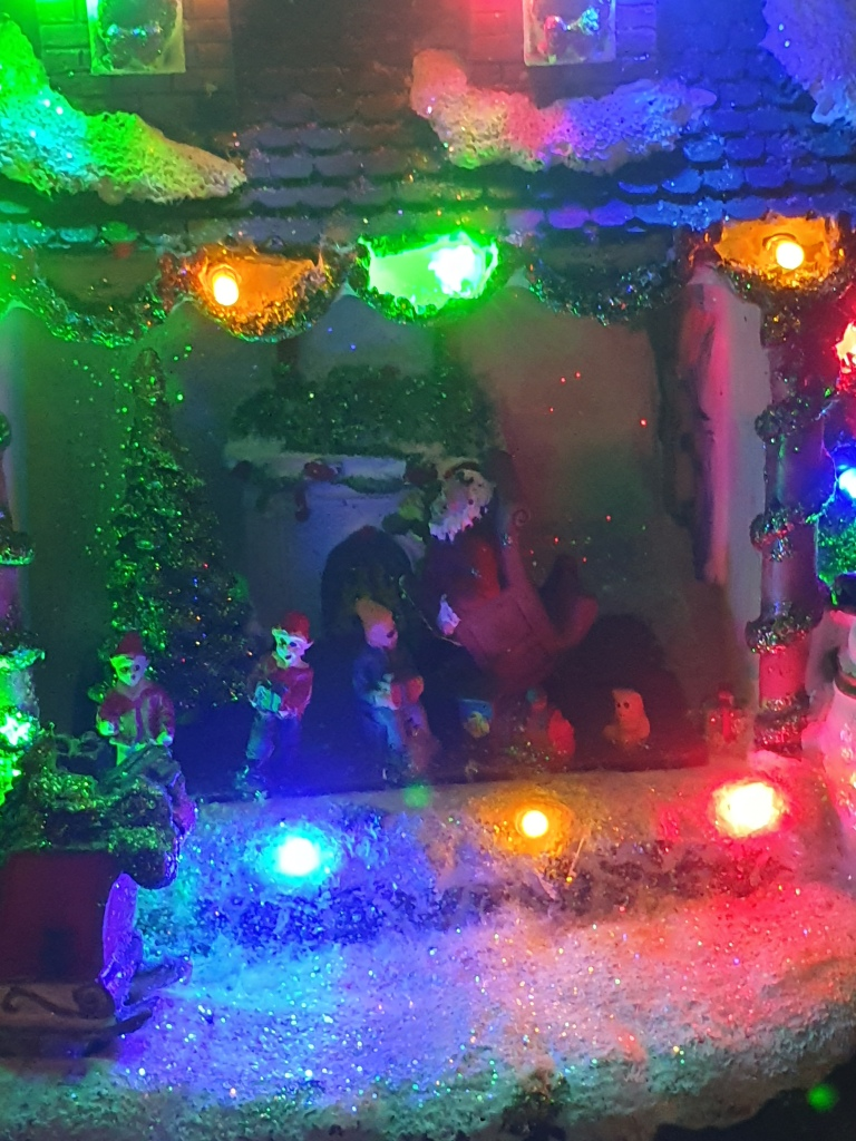 Santa in armchair in his decorated and lit up house; elves