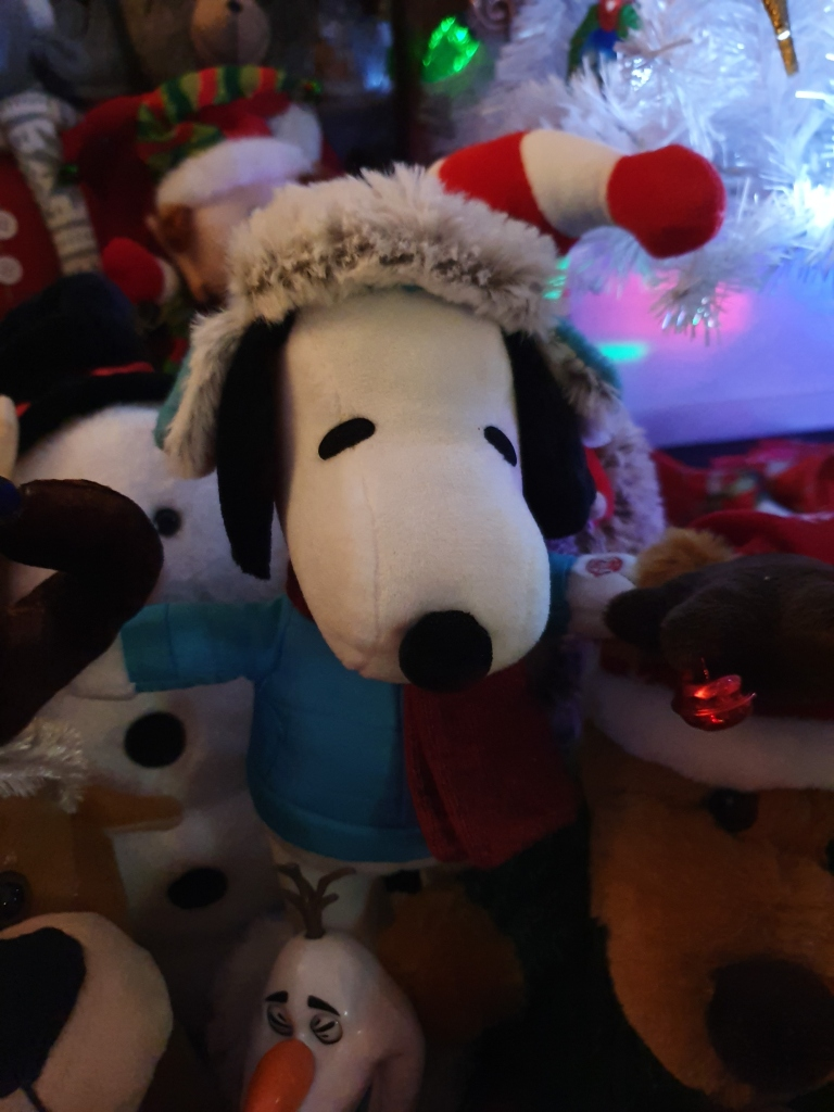 Snoopy soft toy with other toys around; you can see a bit of Olaf's head
