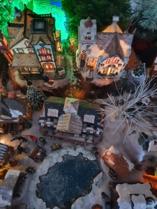 Lit up Christmas village with a view over the lake and of surrounding buildings