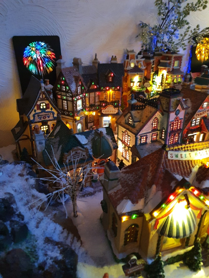 Lit up, snow-clad Christmas village with replica fireworks in the background