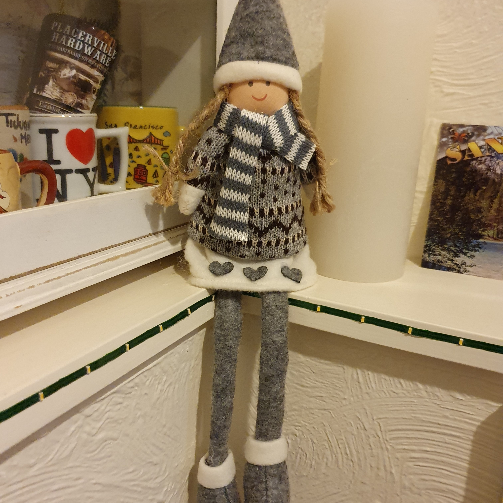 Sitting fabric dolly in grey winter outfit and scarf