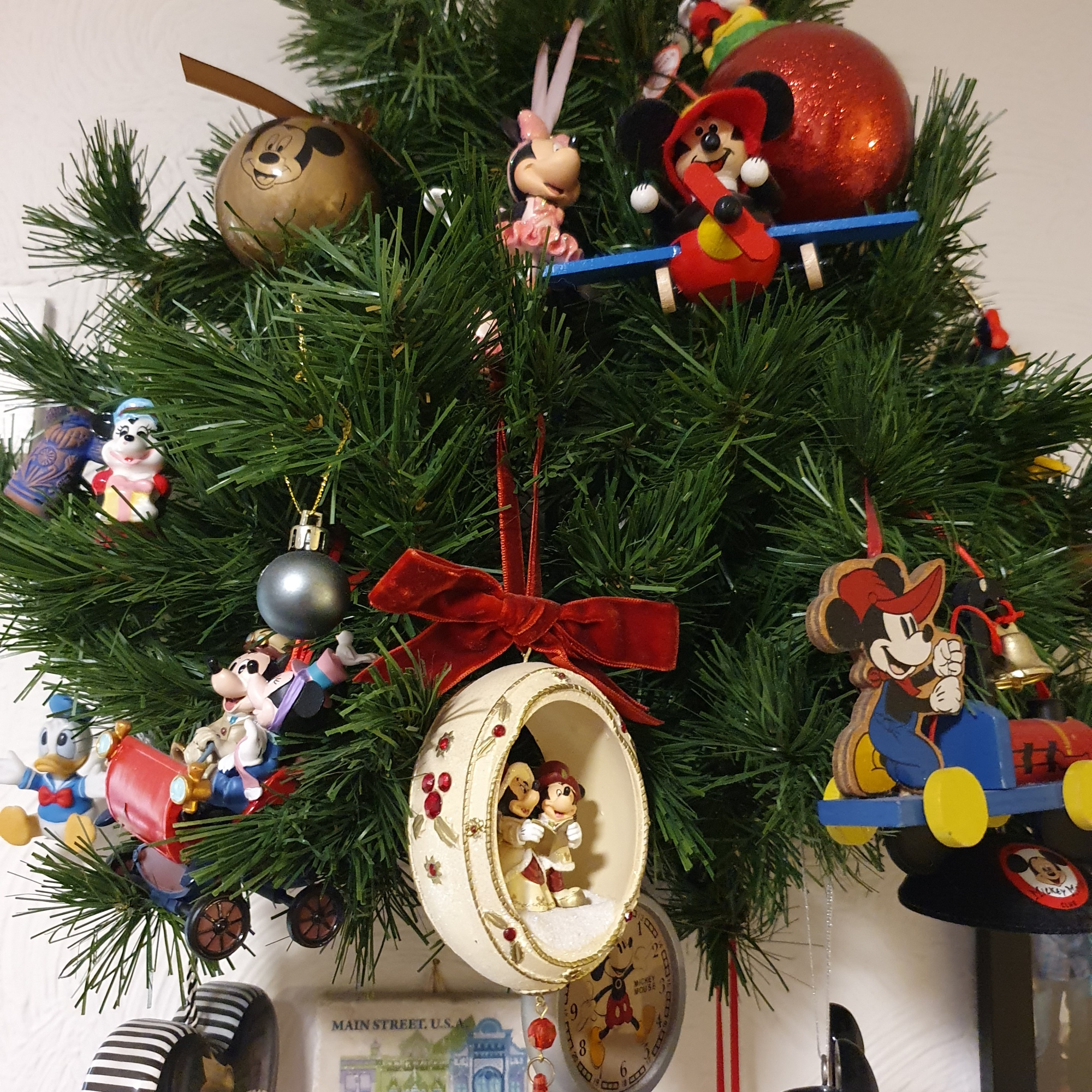 ASmall tree featuring lots of Disney ornaments, mostly Mickey and Minnie