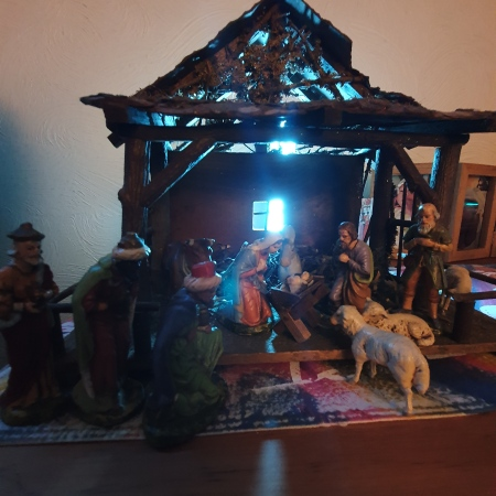 Large rustic stable with the nativity figures: the baby Jesus, Mary and Joseph kneeling, the shepherd and his sheep; the three wise men, animals in the background; light shining through