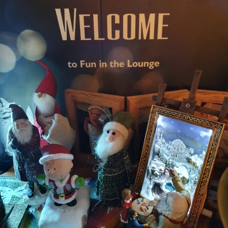 Selection of Santas and other ornaments.in front of the Welcome to Fun in the Lounge sign