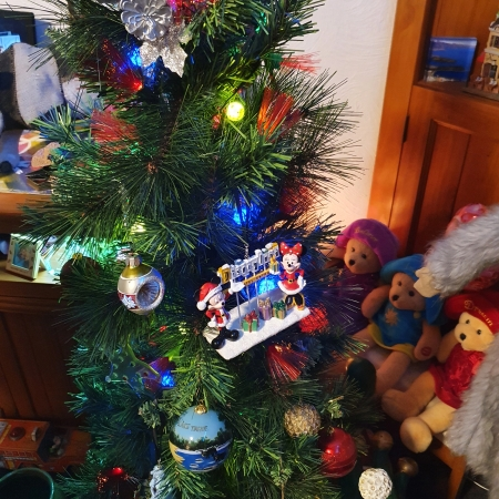 Green Christmas tree with lights and ornaments, including Mickey and Minnie standing with a Disneyland sign and presents; teddy bears in the background