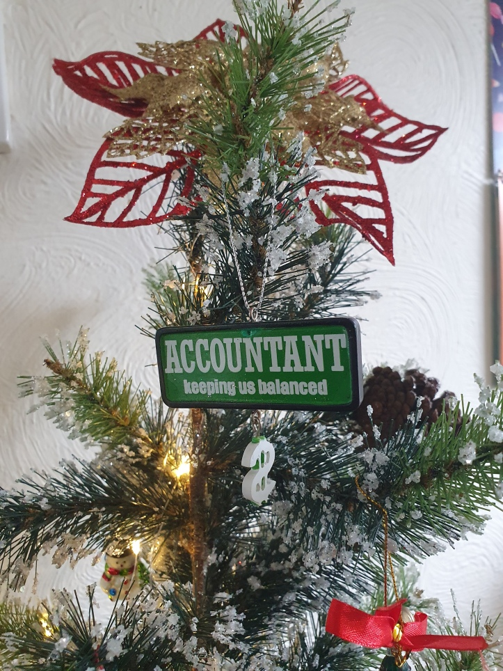 Green tree with sign reading ' Accountant keeping us balanced'